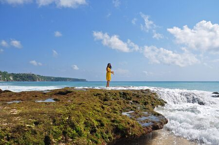 A girl standing in the spilling foam of a wave breaking over the mossy rocks