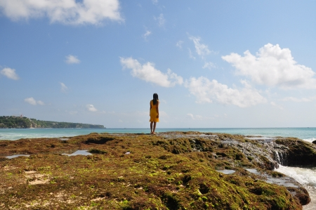 A girl standing on mossy rocks as calm  returns to the sea