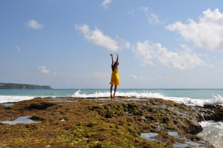A girl is tiptoeing and saluting nature with blue sky and mossy rock