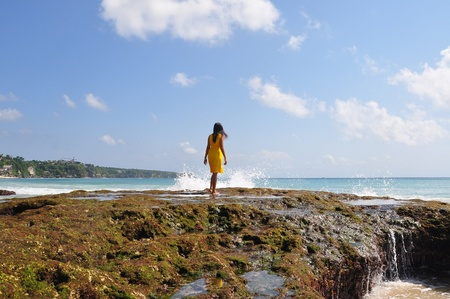 A girl walking towards the waves Stock Photo