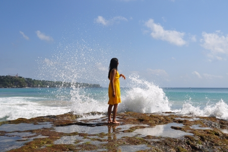 A girl watching the splashing sea over the rock