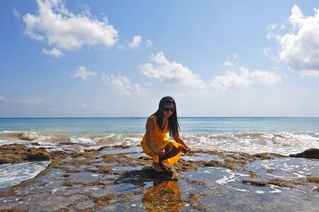A girl squatting on the mossy rock in front of the ocean Stock Photo