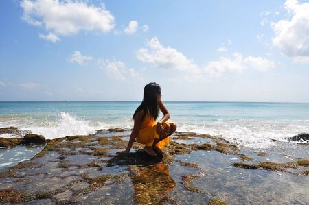 A girl squatting on the mossy rock in front of the ocean