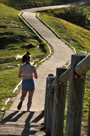 Byron bay Australia, Photo taken at January 2011- A tourist walking back  from the beach it�s a walkway  from a park to beach of cape Byron