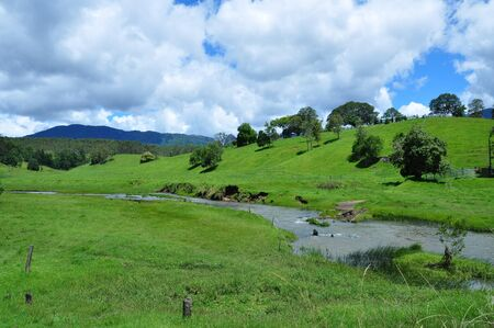 A river stream under the grassy hills  Stock Photo