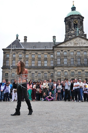 Amsterdam, Holland, Foto taken at June 2012-A crowd in front of the queen palace watching a show by man tied  in chain
