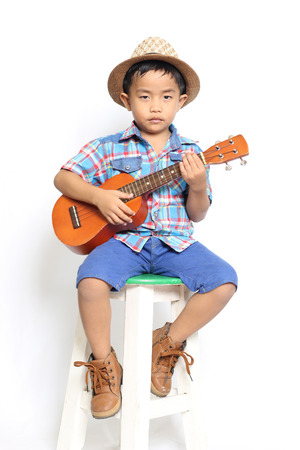 acoustic ukulele: Boy playing acoustic ukulele on a white background.