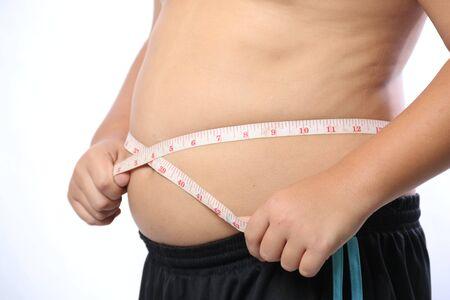 obesidad: Muchacho gordo que mide su vientre con cinta de medición