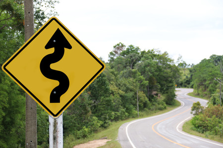 curvaceous: Winding road sign in the forest and mountain Stock Photo