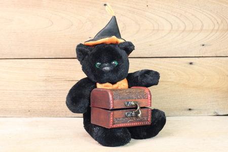 valentine s day teddy bear: Black Bear holding onto a wooden treasure chest. Stock Photo
