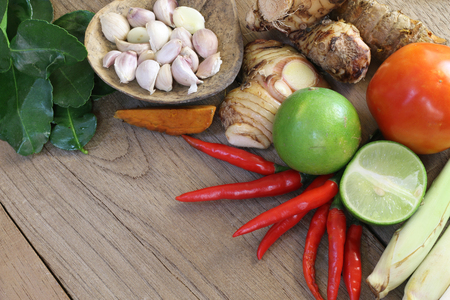 Thailand Food Ingredients: lemon, lime, galangal, ginger ,, tomato, mango leaves the dungeon, garlic on a wooden floor. Stock Photo
