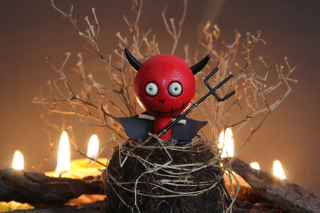 devil: Halloween Devil Doll on black background with dead trees and fire. Stock Photo