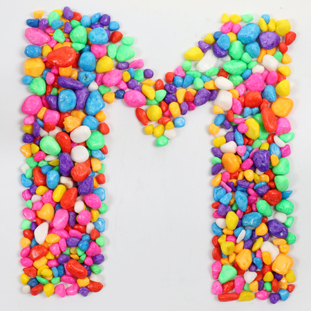 literally: Colored stones arranged in a letter M. Stock Photo
