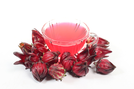 malvales: Roselle fruits against a cup of Roselle tea on white background.