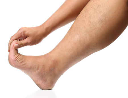 the topical: Man hands are squeezing the toes to wake topical pain from his injuries on white background. Stock Photo