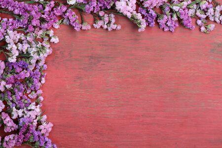 blooming  purple: Red flowers on a wooden floor.