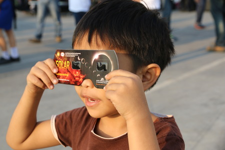 looking glass: Chiangmai, Thailand - March 9, 2016: Thailand boy viewing a solar eclipse in Chiang Mai, Thailand.