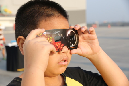 Chiangmai, Thailand - March 9, 2016: Thailand boy viewing a solar eclipse in Chiang Mai, Thailand.