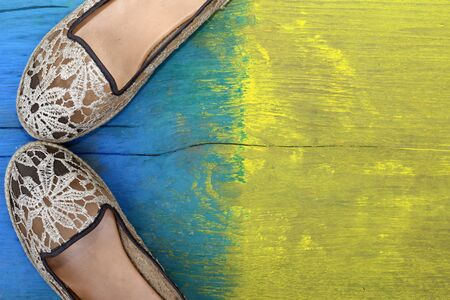 wooden floors: Womens shoes on wooden floors, blue and yellow.