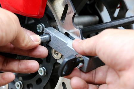 lock and key: Key lock disk brakes motorcycle. Stock Photo