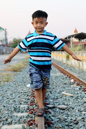 hand rails: Boy walking on railroad tracks