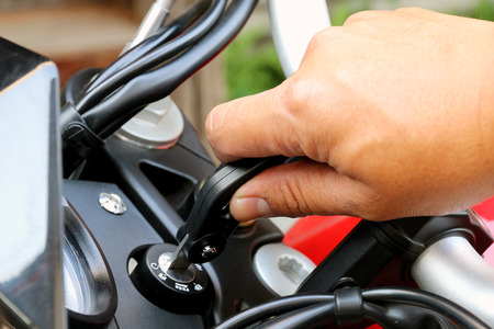 ignition: Pilot inserting the key and starting the engine.motorcycle ignition action.