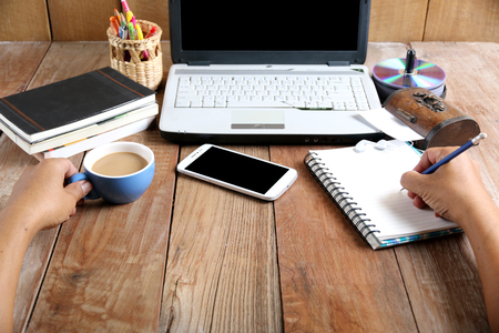 Man working on a computer, a desk, phone, address book, Waupaca, headphones, and his right hand holding his left hand holding a pencil cup. Stock Photo