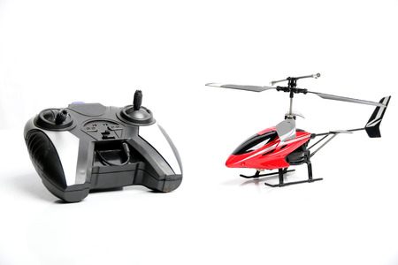 controlled: Remote controlled helicopter with controlling handset, isolated on white background