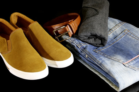Shirts, jeans, shoes and polishing cart. Men  isolated on a black background. Stock Photo