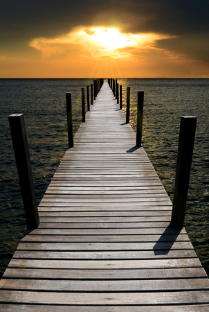 The wooden bridge in the sea at sunset is beautiful.