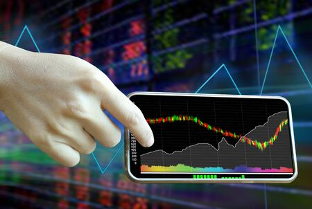 Woman hand using smartphones to monitor investment in the stock market.