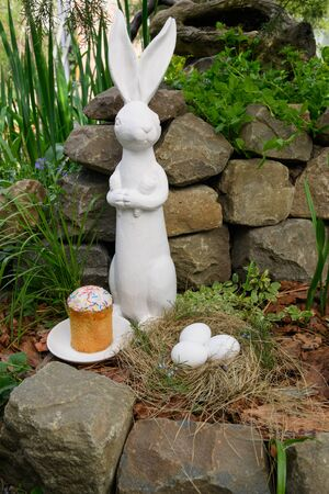 Easter white rabbit in outdoor. white Easter eggs and Easter cake lie on a white saucer. on the stone wall backround. No people. Concept of the Christian holiday of Holy Easter Stock Photo