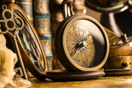 Antique compass on the background of a candle with a key and books. Vintage style. 1565 old map of the year. Banque d'images