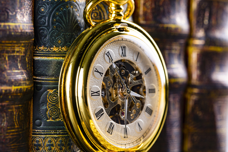 Antique clock on the background of vintage books. Mechanical clockwork on a chain.