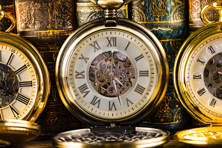 Antique clocks on the background of vintage books. Mechanical clockwork on a chain. Imagens