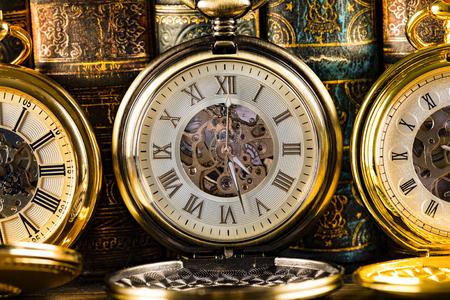 Antyczne zegary na tle starych książek. Mechaniczny mechanizm zegarowy na łańcuszku. Zdjęcie Seryjne