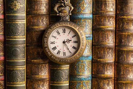 Antique clock on the background of vintage books. Mechanical clockwork on a chain. Standard-Bild