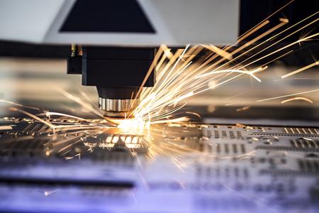 Fresatrice cnc. Lavorazione e taglio laser per metallo in ambito industriale con refrigerante. Esposizione industriale di macchine utensili.