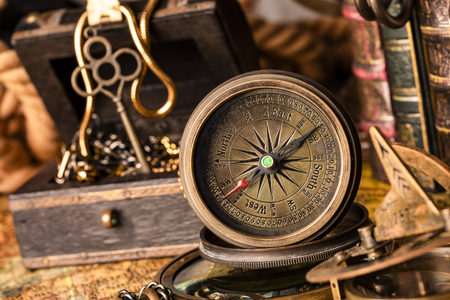 Antique compass on the background of a treasure chest with gold and books. Vintage style. 1565 old map of the year.