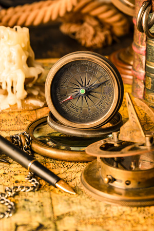 Antique compass on the background of a candle and books. Vintage style. 1565 old map of the year.