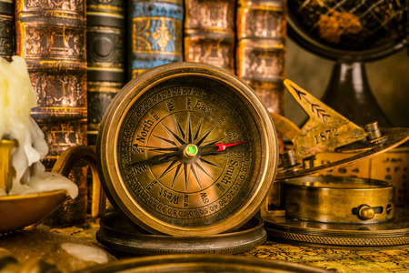 Antique compass on the background of the globe and books. Vintage style. 1565 old map of the year. 写真素材