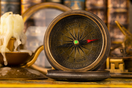 Antique compass on the background of the magnifying and books. Vintage style. 1565 old map of the year. 写真素材