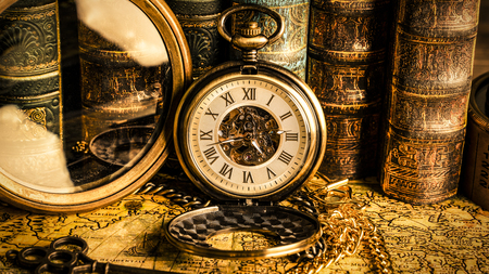 Antique clock on the background of a magnifying glass and books. Vintage style. 1565 old map of the year. Imagens