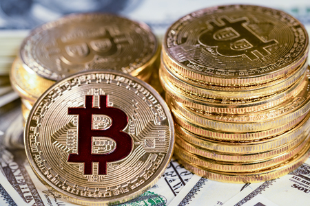 Pile bitcoin btc bit-coin lie on hundred-dollar bills of United States. Mining cryptocurrency.