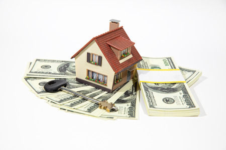 A small house lies on a fan of hundred dollar bills. The keys to the purchased house. Reduced copy of the house on a white background. Banque d'images