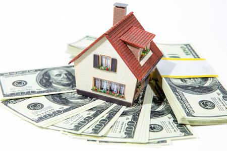 A small house lies on a fan of hundred dollar bills. The keys to the purchased house. Reduced copy of the house on a white background. Banco de Imagens