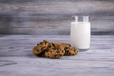 A stack of chocolate chip cookies lies near a glass of milk. Calcium-rich milk.
