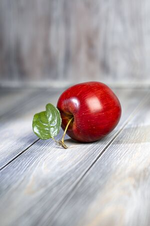 Red ripe apple lies on a wooden light table.
