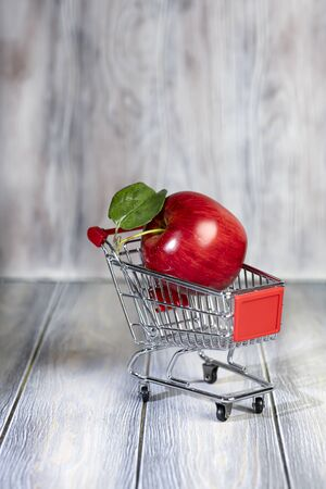 A red ripe apple lies in a shopping trolley. 写真素材