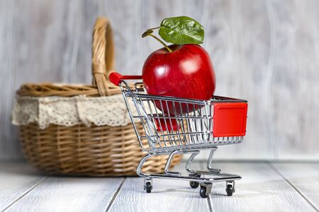 A ripe red apple lies in a shopping trolley against the background of a basket.